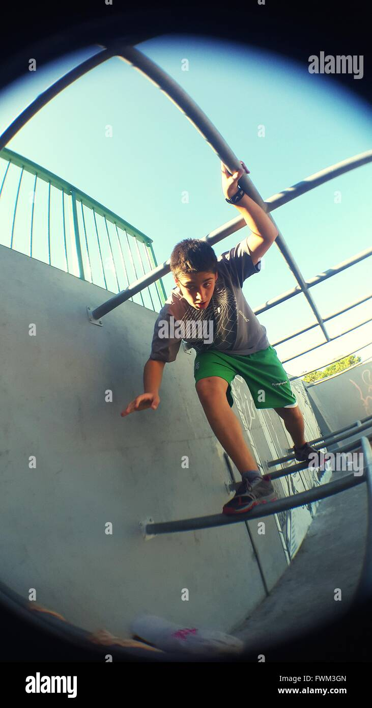 Low Angle View Of Boy Playing On Monkey Bars At Park - Stock Image