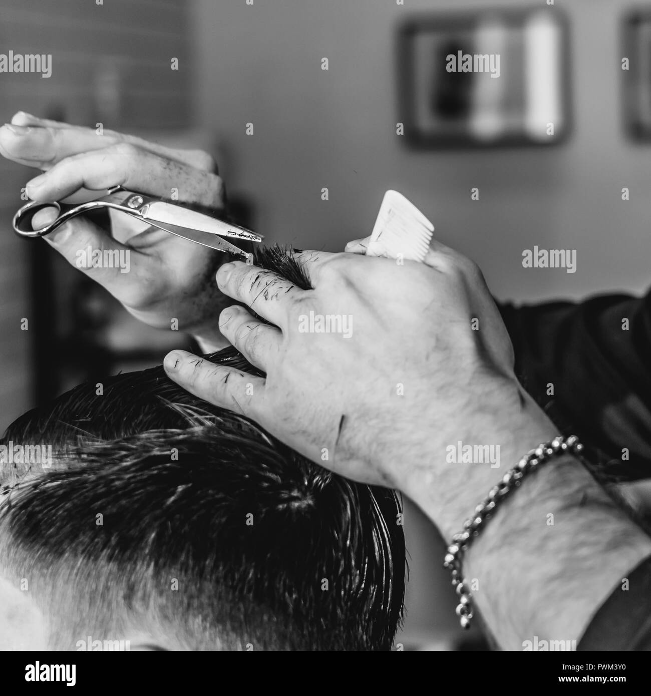 Cropped Image Of Hairdresser Hand Cutting Hair - Stock Image
