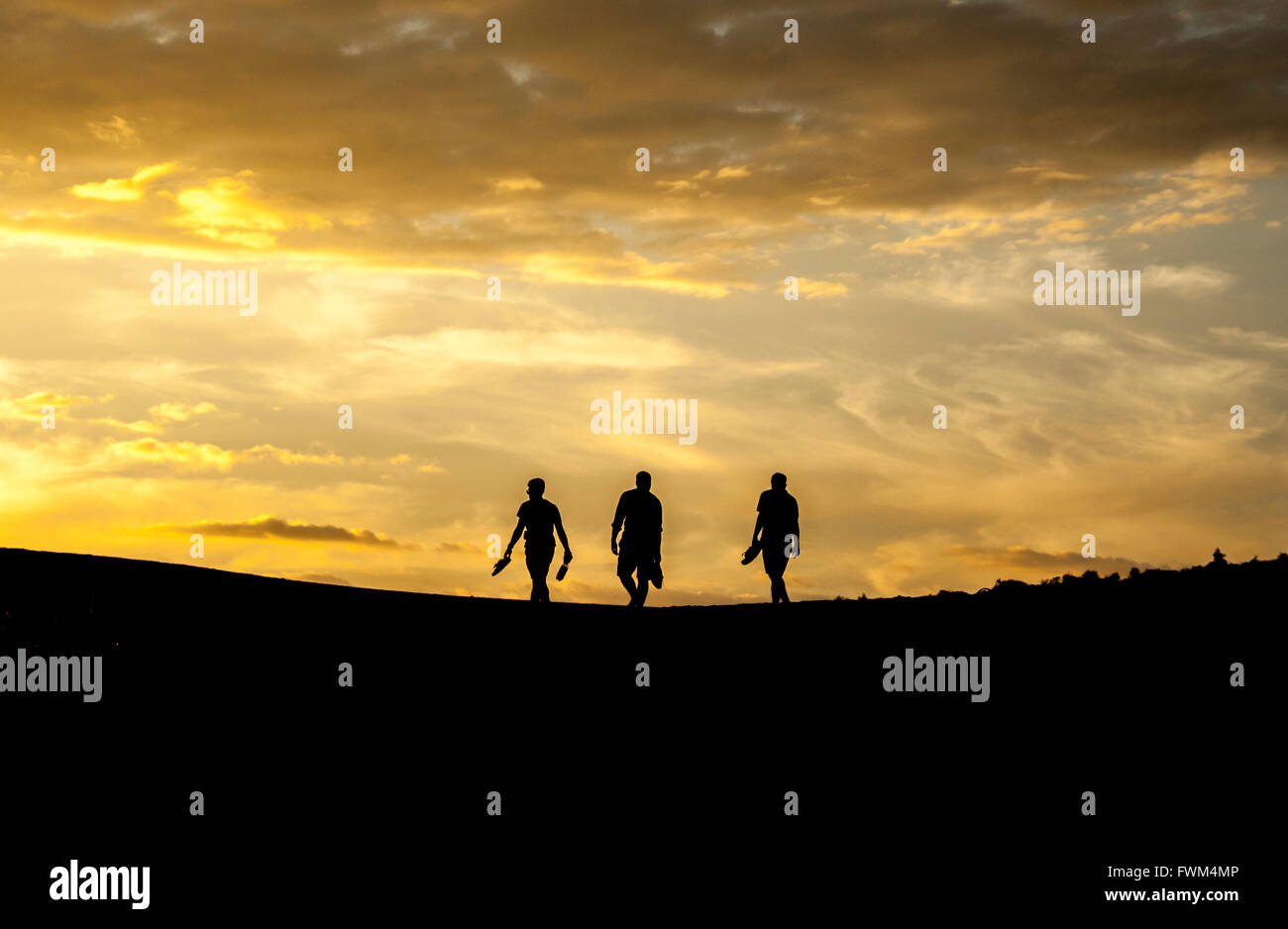 Silhouette Men Walking On Hill Against Sky During Sunset - Stock Image