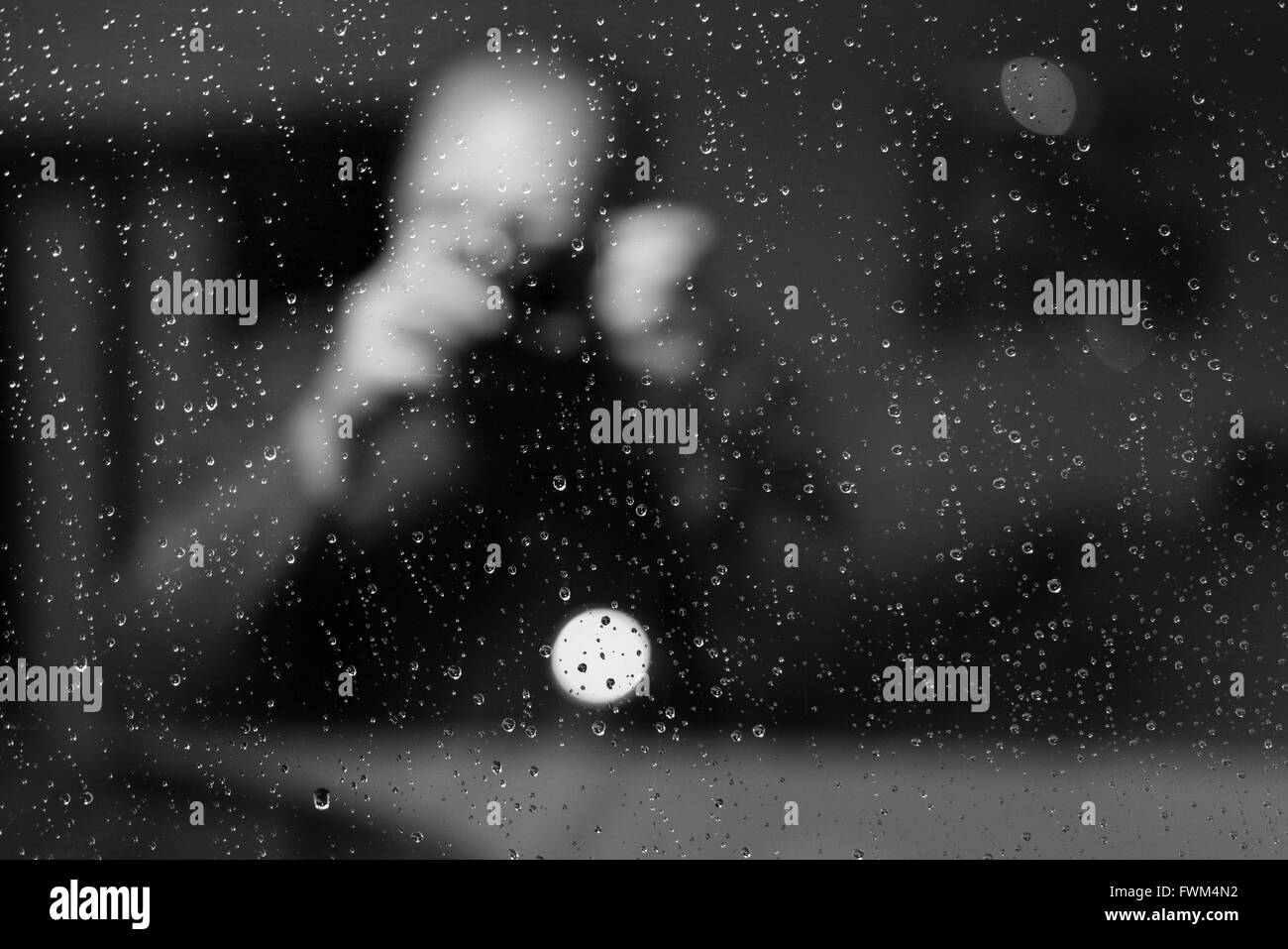 Man Seen Through Wet Glass Window - Stock Image