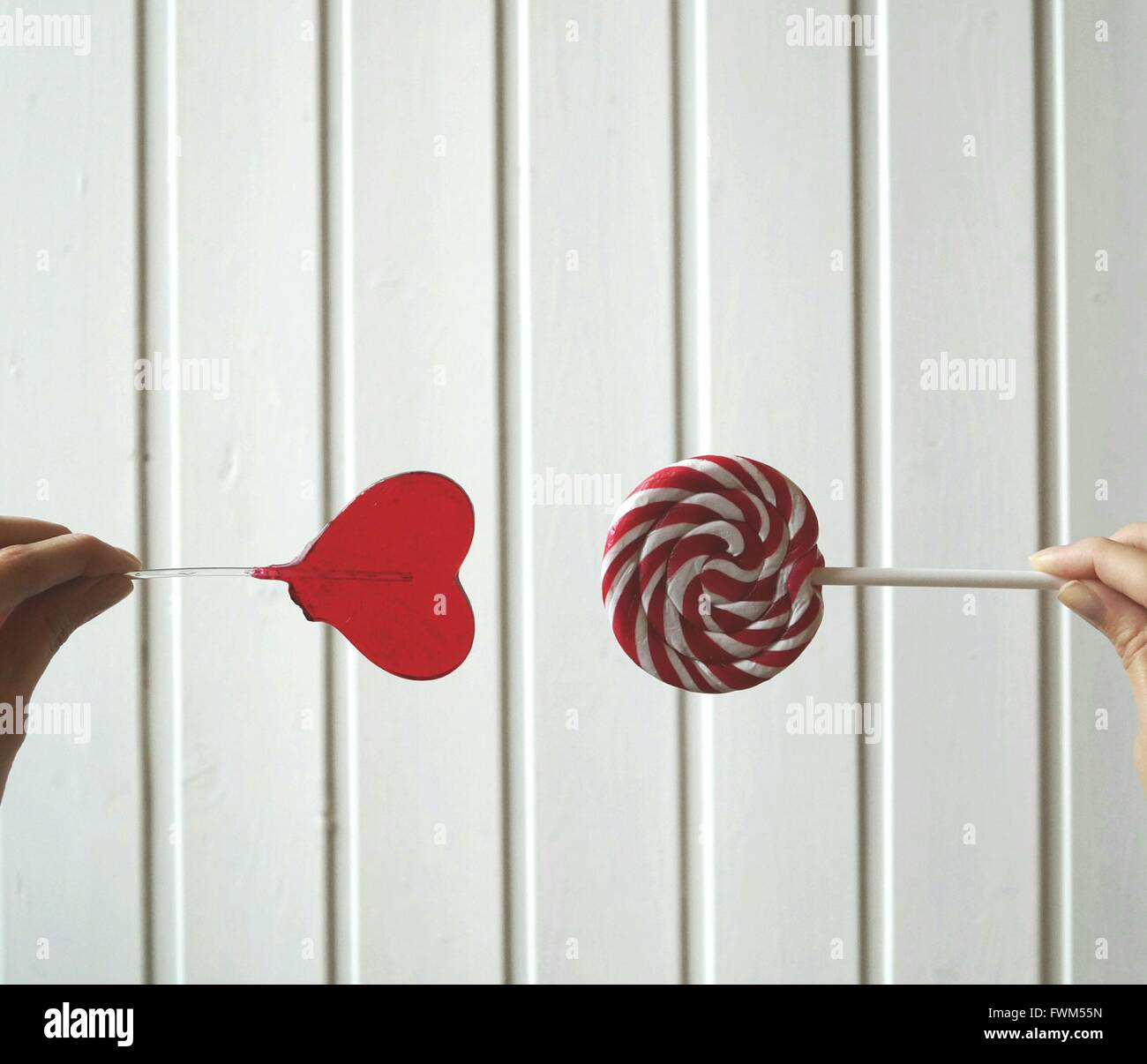 Cropped Woman Hands Holding Candies Against White Wall - Stock Image