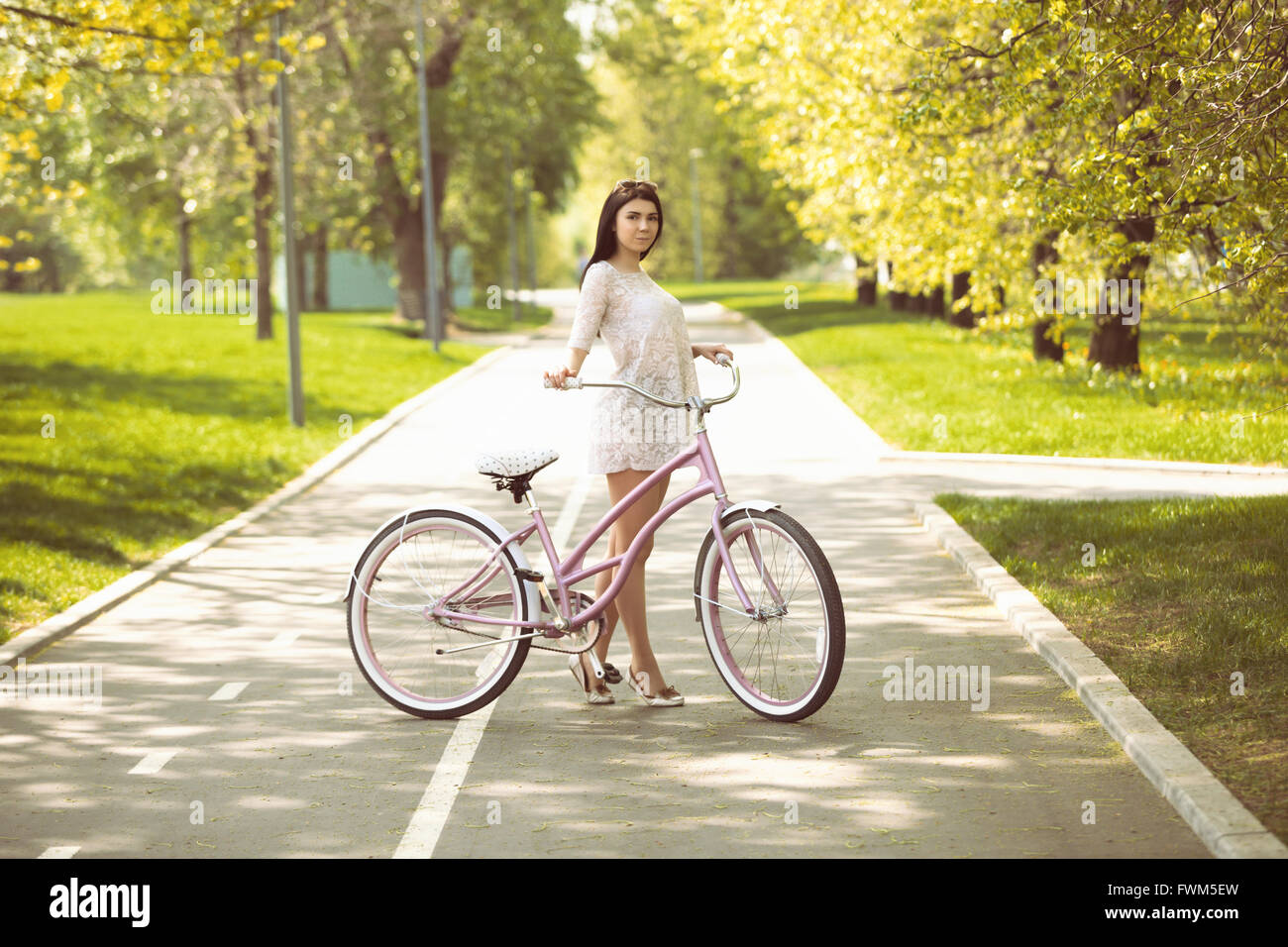 Young brunette girl in sundress riding a bicycle in green park at bright spring or summer day. Leisure time, good - Stock Image