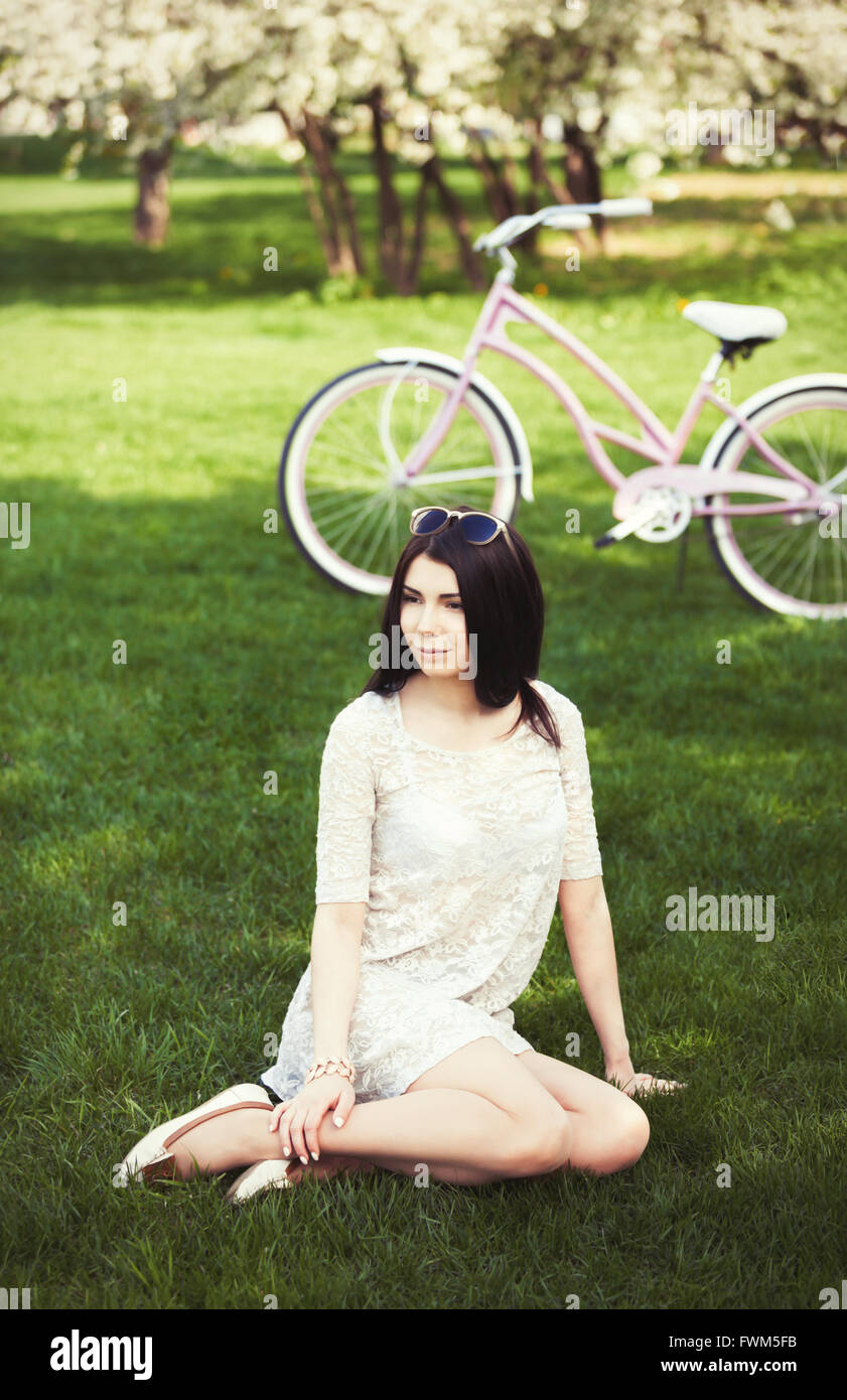 Attractive young girl with pink bicycle spending leisure time in green park at bright summer or spring day. Model - Stock Image