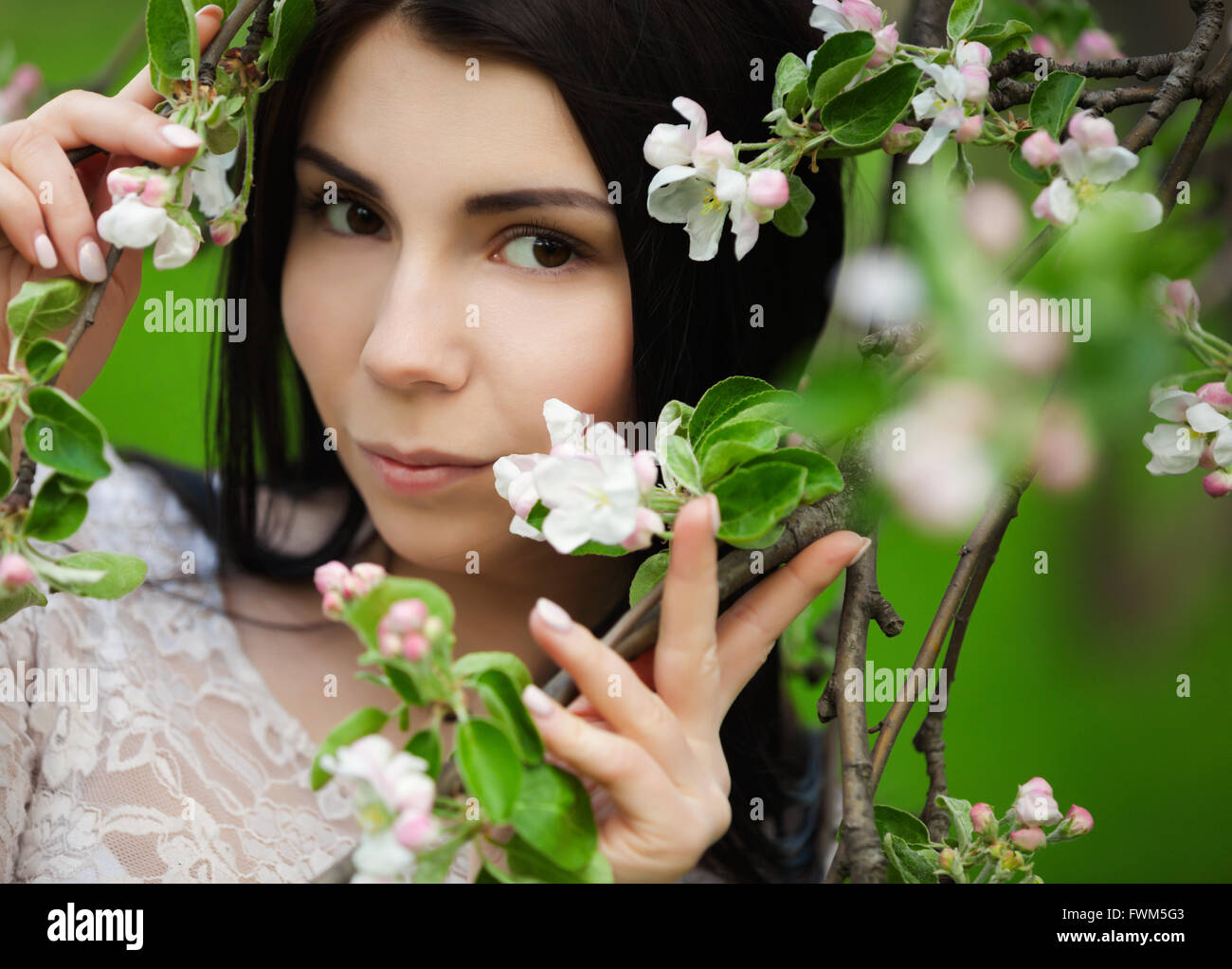 Attractive young woman posing with lilic flowers in green park at bright spring day in her leisure time. Great portrait - Stock Image