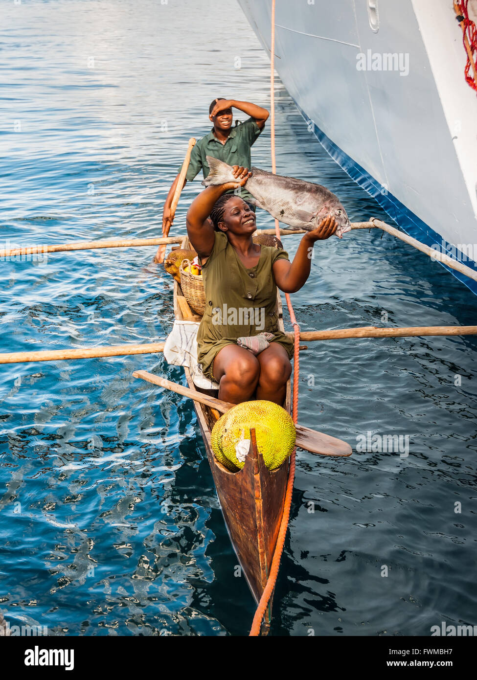 Malagasy vendors from their outrigger canoe offer crabs, fish and tropical fruits - Stock Image