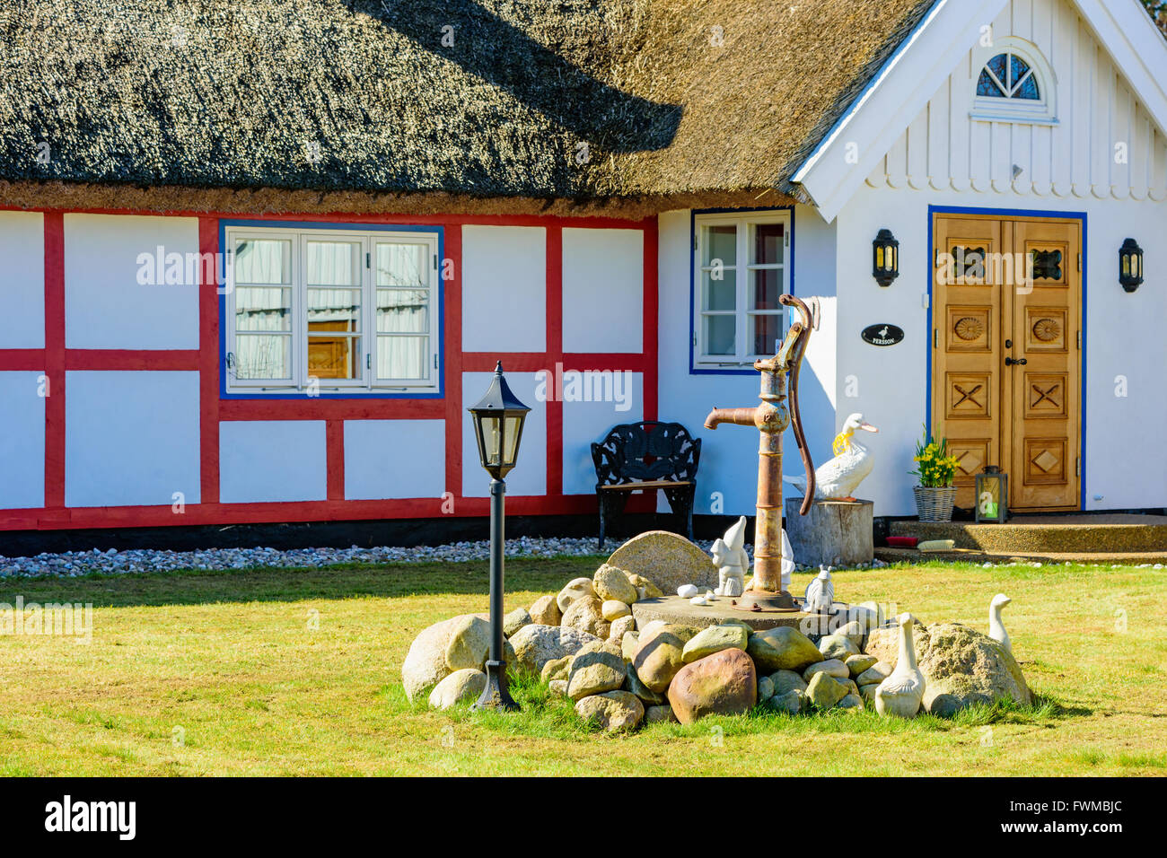 Kivik, Sweden - April 1, 2016: Lovely garden ornamentals around a water pump. Some gnomes, a snail and some ducks - Stock Image