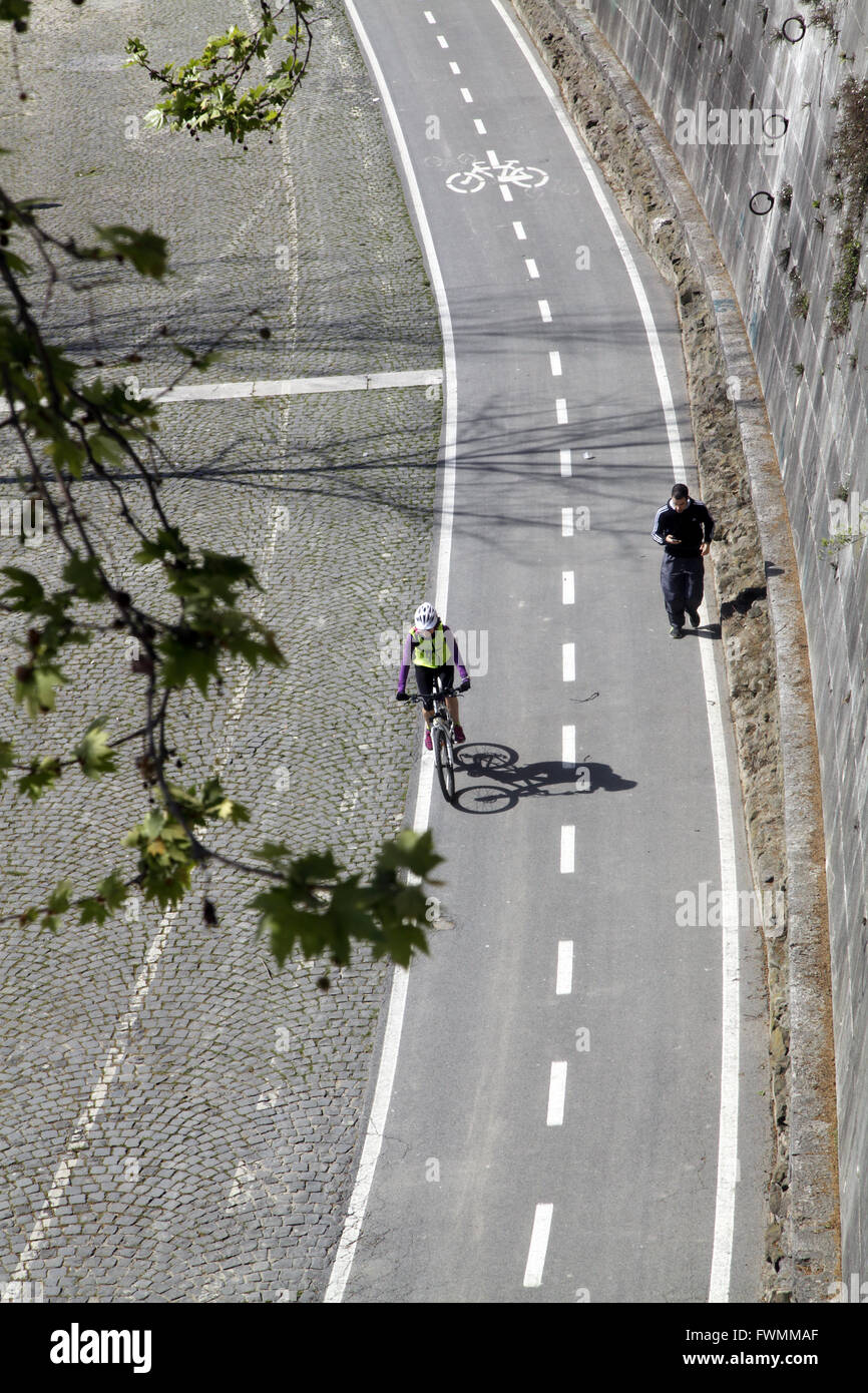 Urban cyclist riding cycle lane along the Tevere river in Rome,Italy - Stock Image