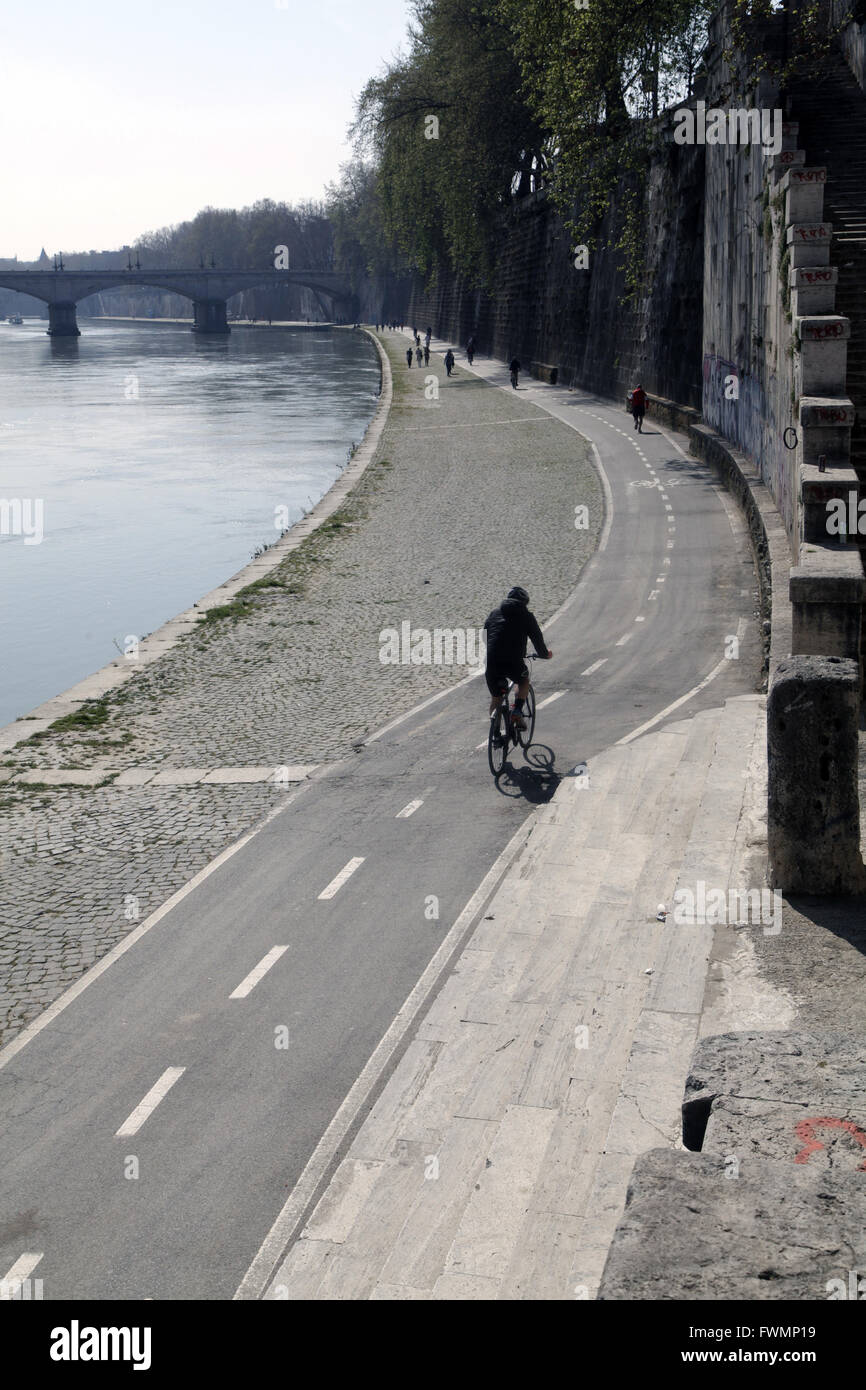 Urban cyclist riding cycle lane along the Tevere river in Rome, Italy - Stock Image