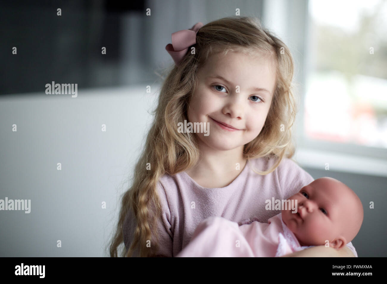 portrait of girl with baby doll wrapped in towel. kid, happiness, toy, childcare. - Stock Image