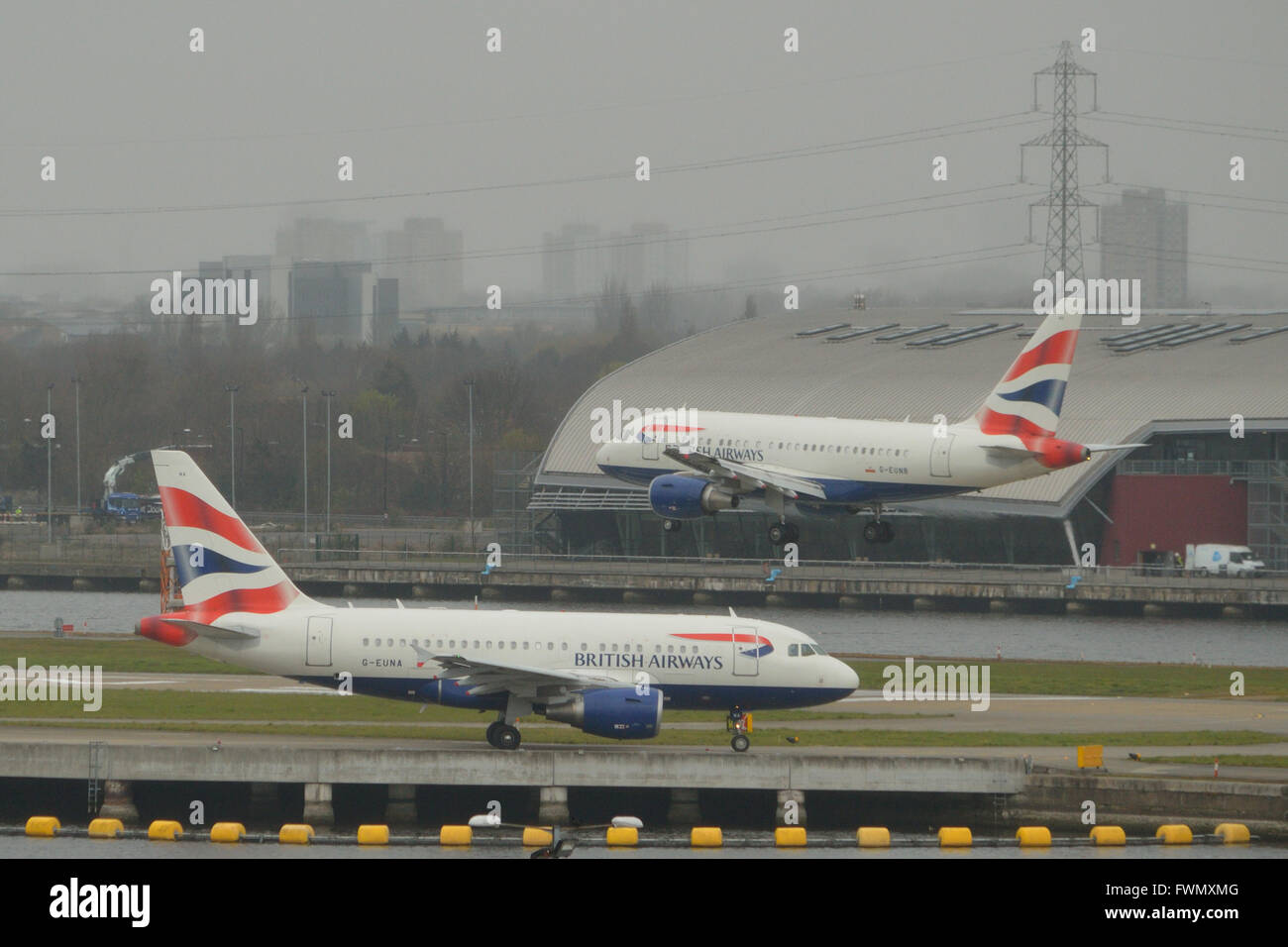 The two British Airways A318 'Baby Bus' jets at London City Airport - G-EUNA waiting to depart as G-EUNB - Stock Image