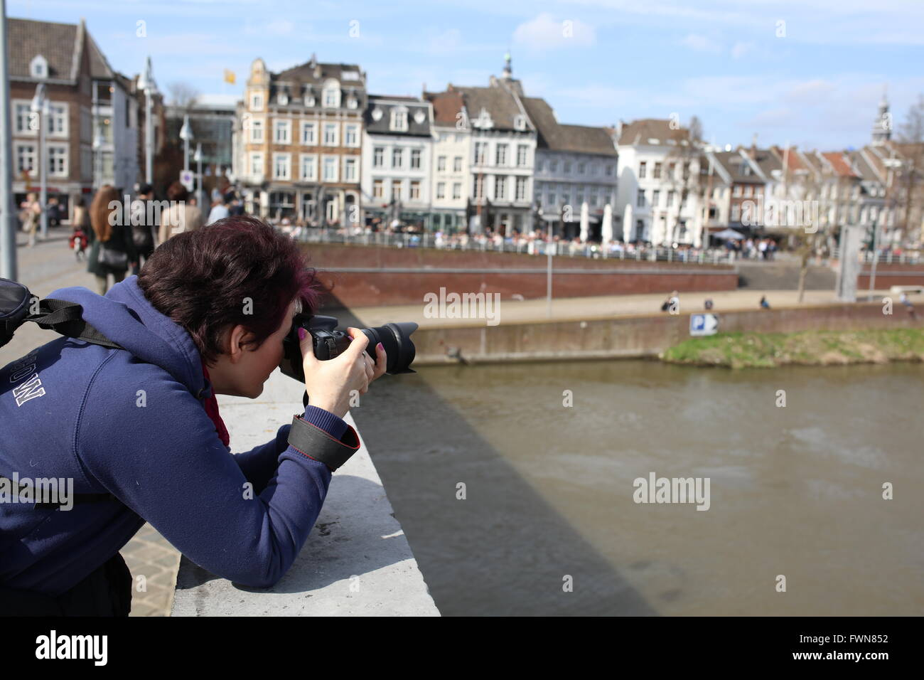 Maastricht, Netherlands, tourist taking photo from bridge, model release possible - Stock Image