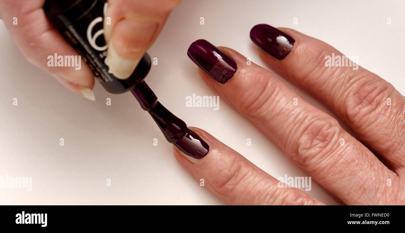 Plum colored nail varnish being painted onto fingernails - Stock Image