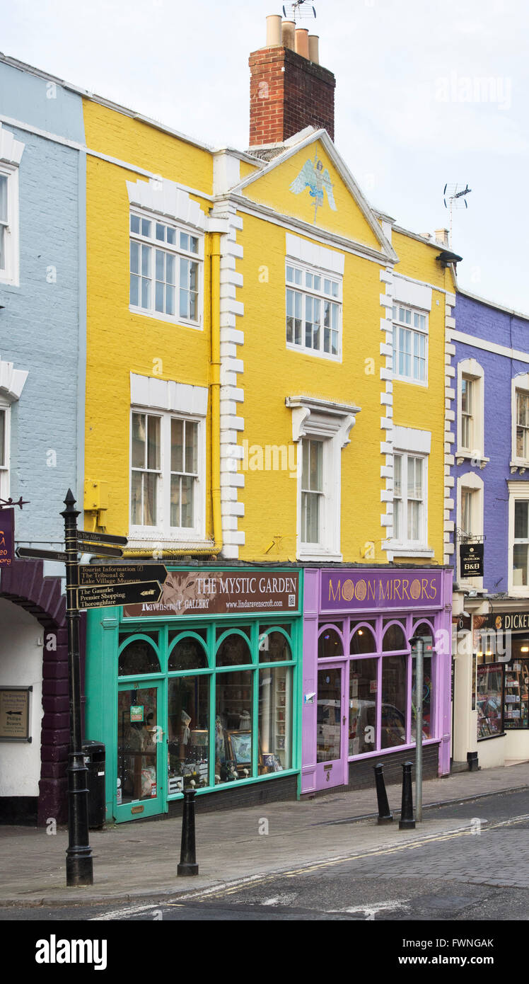 Colourful shop fronts in the high street. Glastonbury, Somerset, England - Stock Image