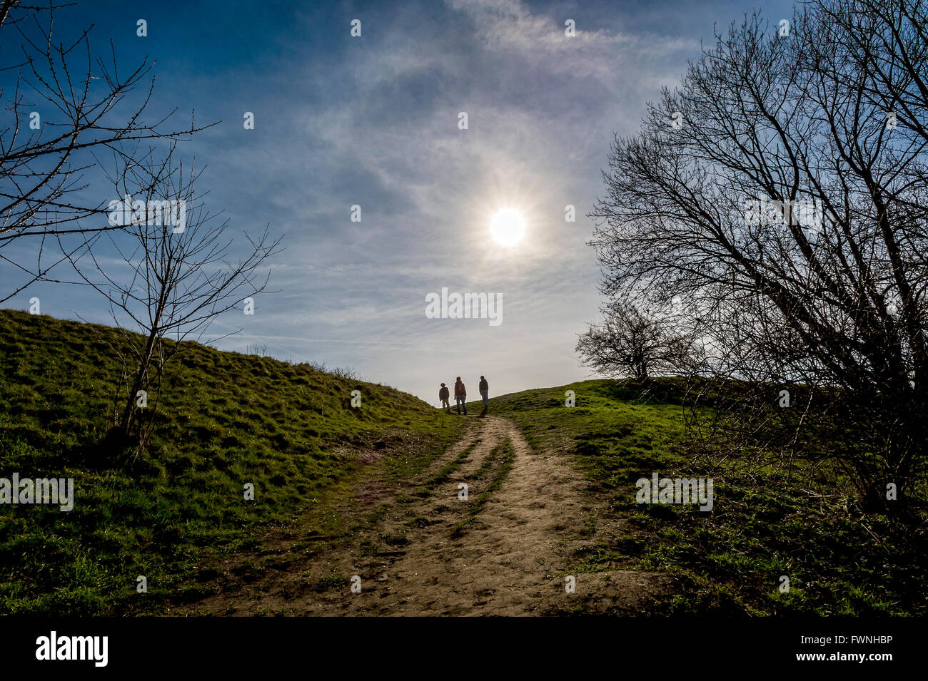 three persons in contra light going on the way in spring country side apart lens - Stock Image