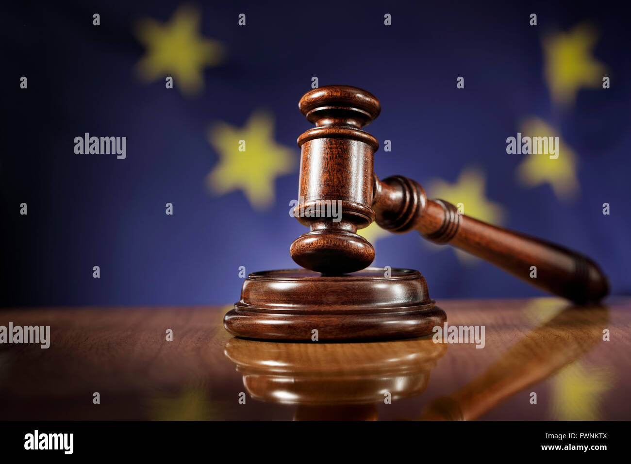 Mahogany wooden gavel on glossy wooden table. Flag of European Union, EU,  in the background. - Stock Image
