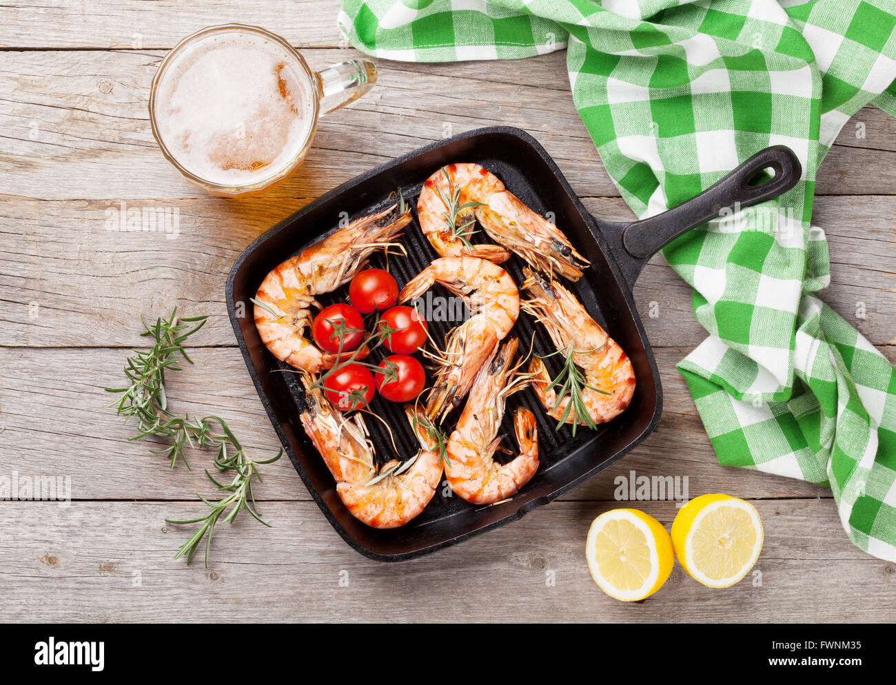 Grilled shrimps on frying pan and beer. Top view - Stock Image