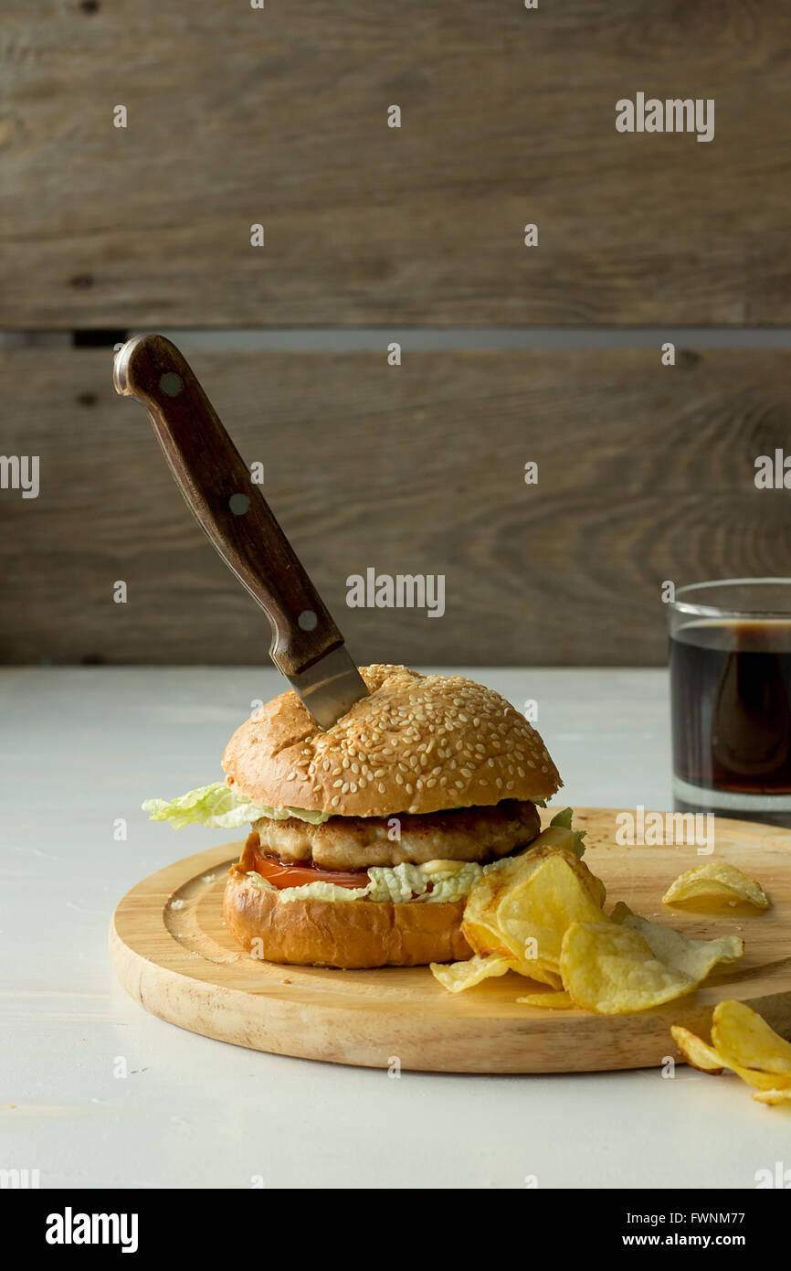 Knife in burger and chips  vertical selective focus Stock Photo