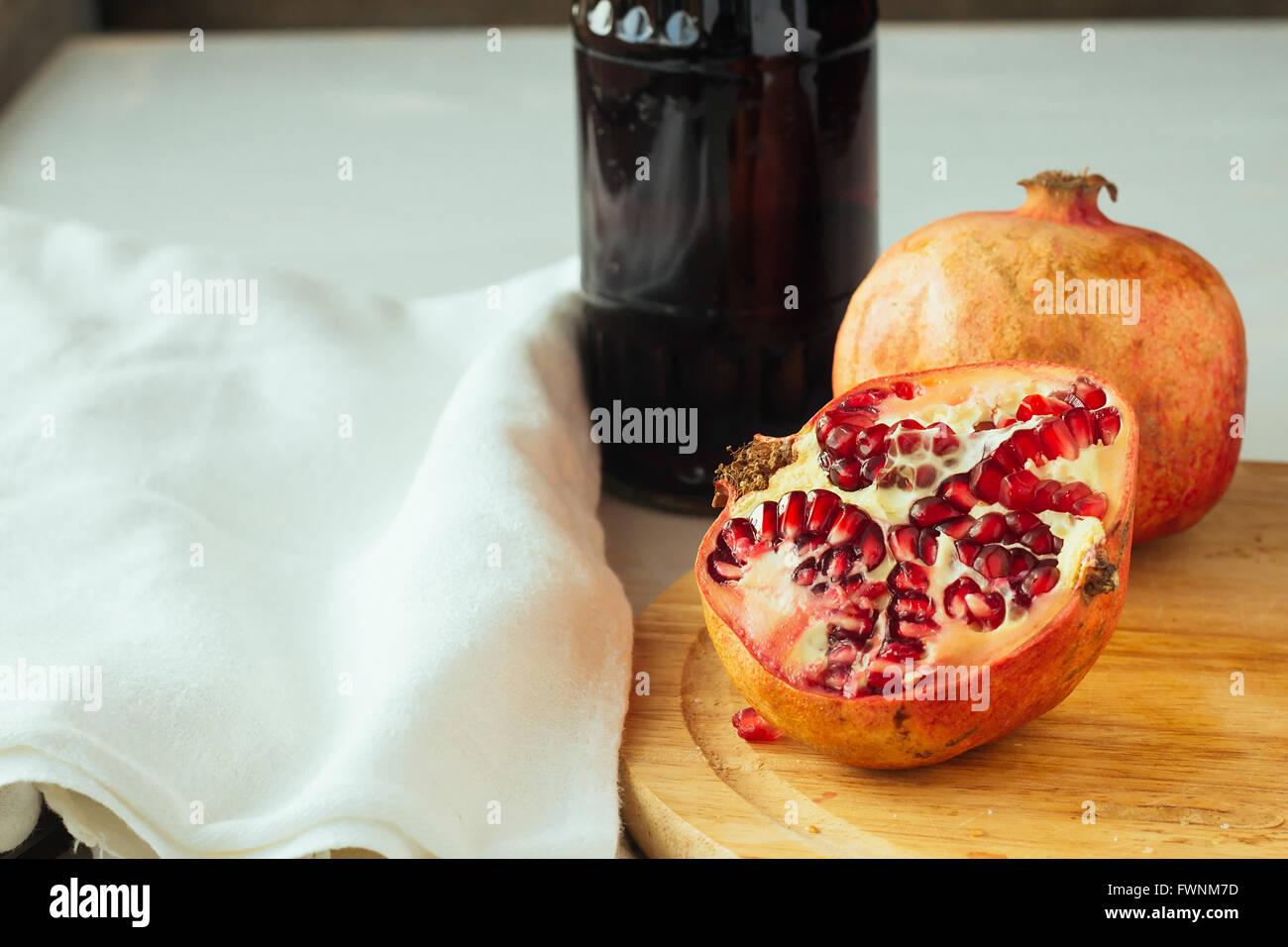 Cut pomegranate and juice bottle selective focus - Stock Image