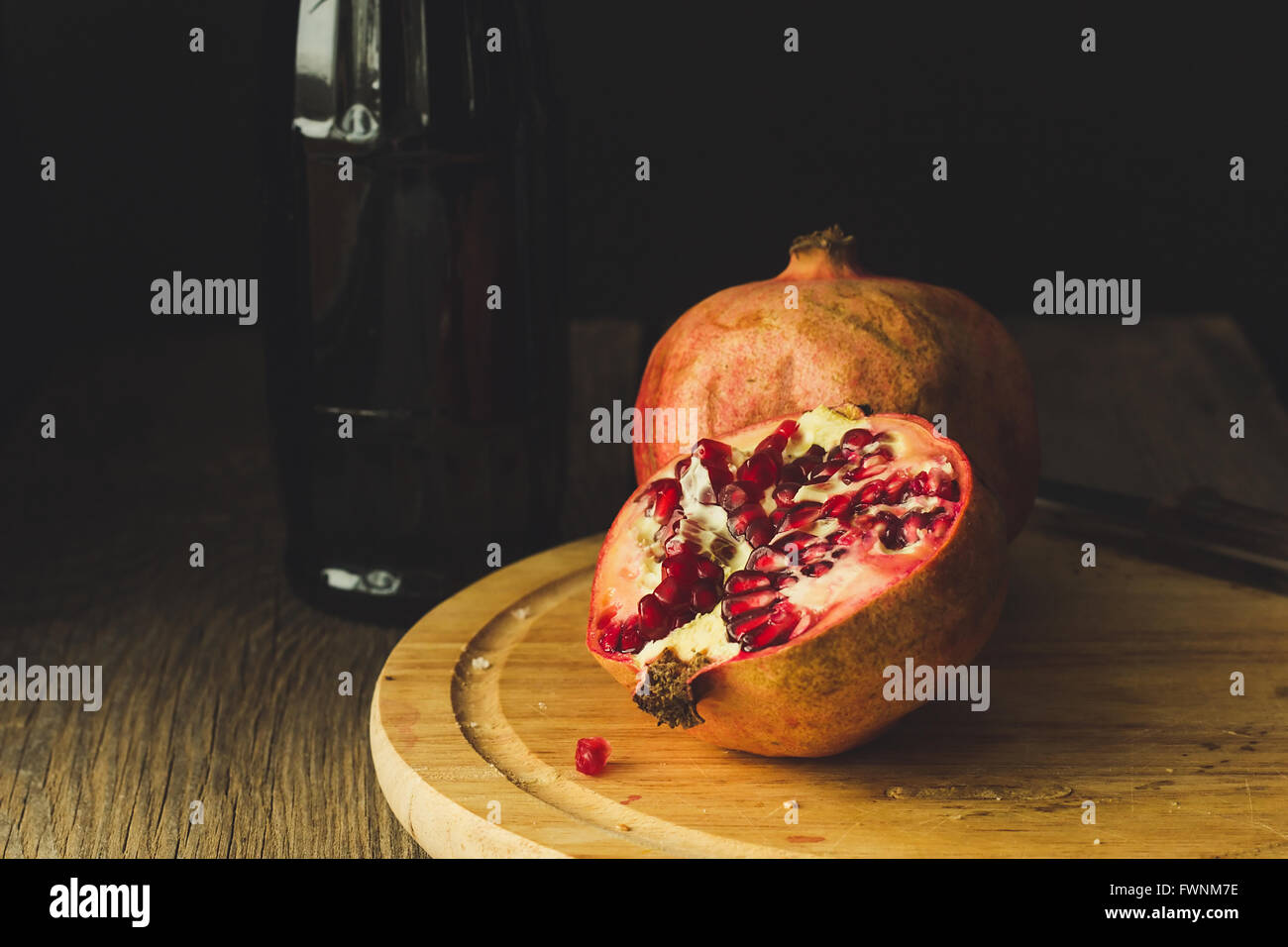 Pomegranates and bottle selective focus low key - Stock Image