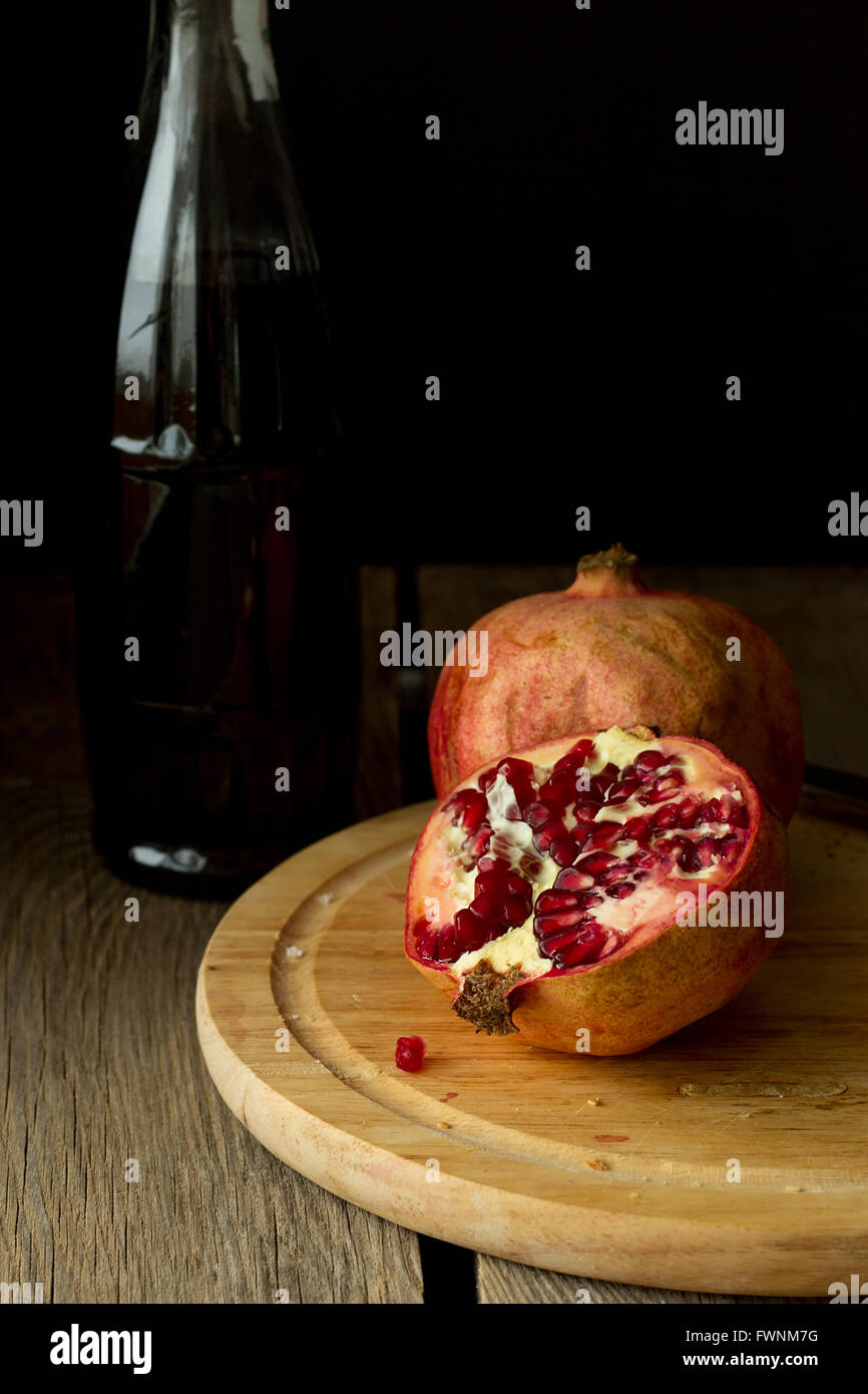 Pomegranates and bottle vertical selective focus - Stock Image