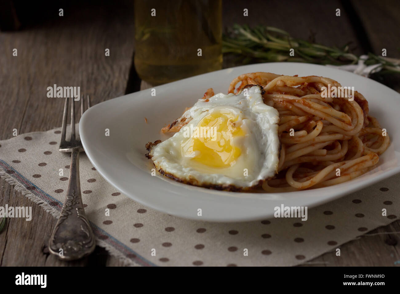 Spaghetti with tomato paste and fried egg selective focus - Stock Image