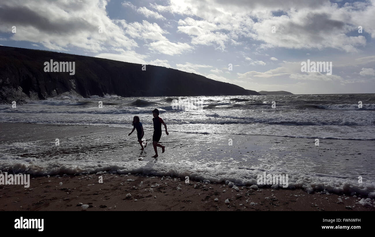 Mwnt Beach, Cardiganshire, West Wales, UK. 6th April, 2016. Weather Children play in the sea during the Easter Holidays - Stock Image