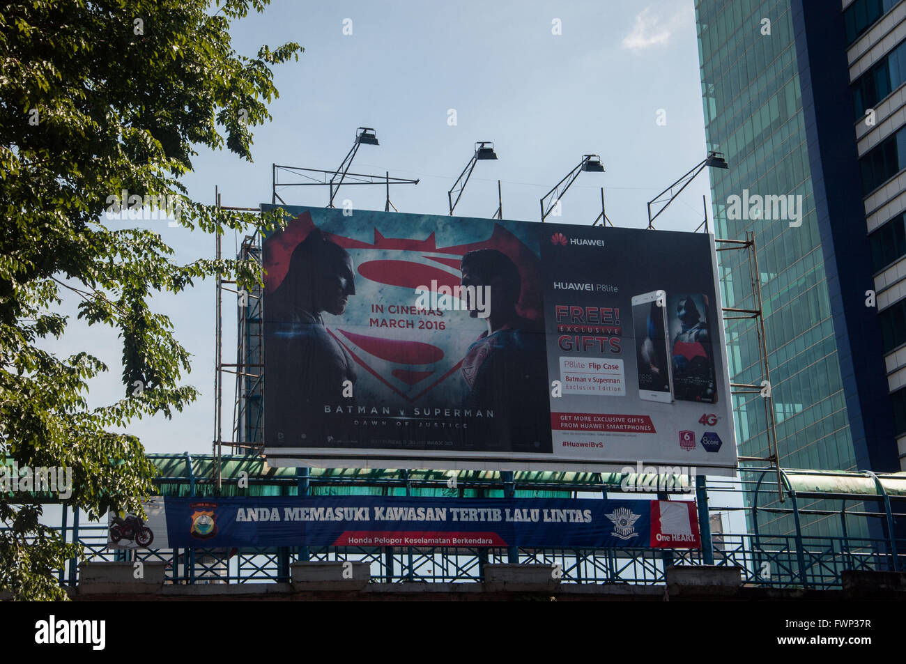 Promotion billboard of Batman vs Superman movie attached on the street-crossing bridge at Sudirman Street. Bank - Stock Image