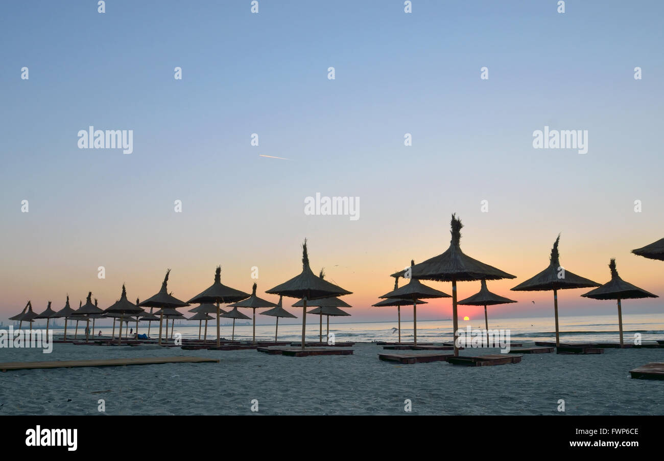 Silhouettes of parasols. The sun rises over the sea. - Stock Image