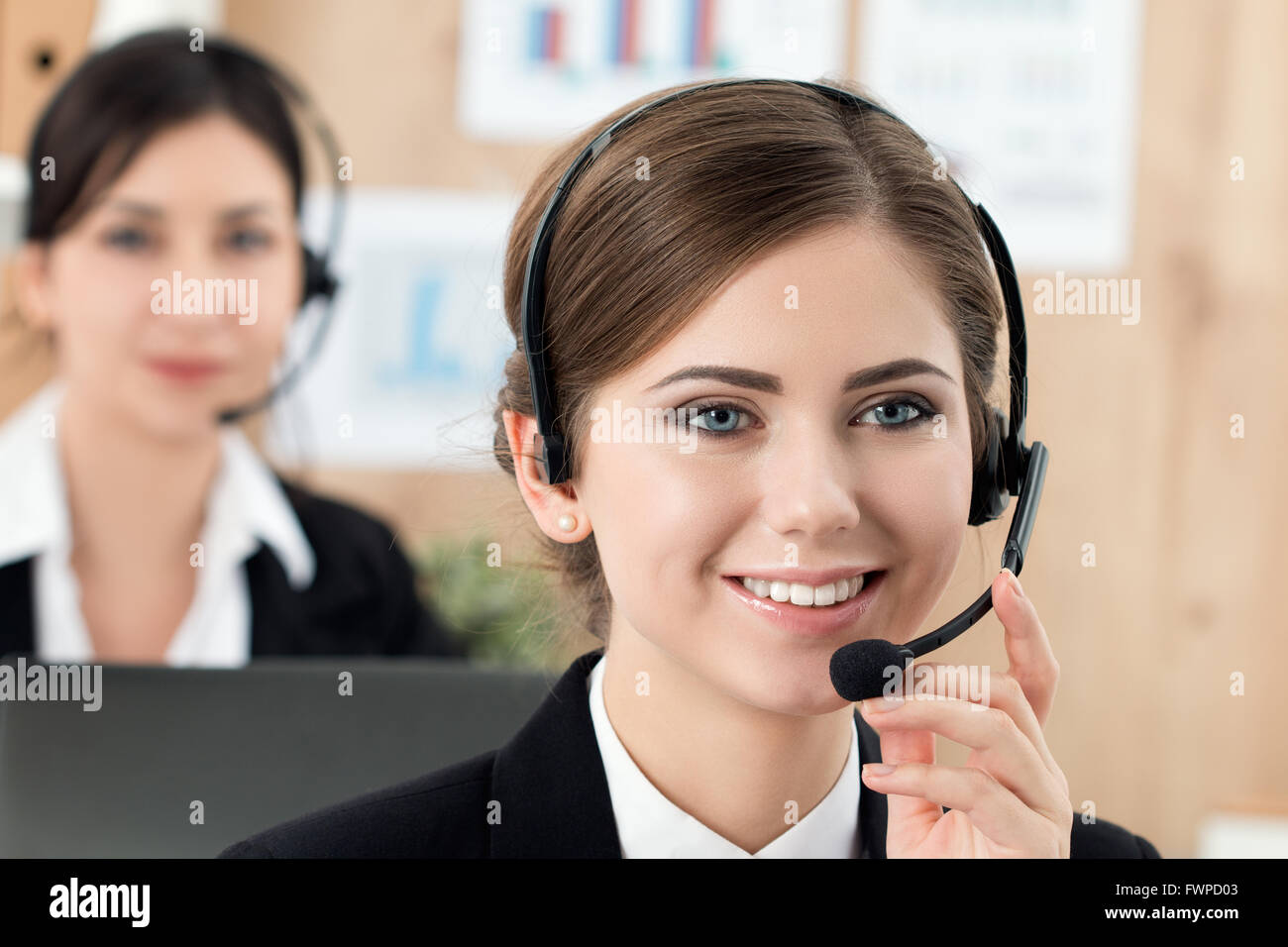 Portrait of call center worker accompanied by her team. Smiling customer support operator at work. Help and support - Stock Image