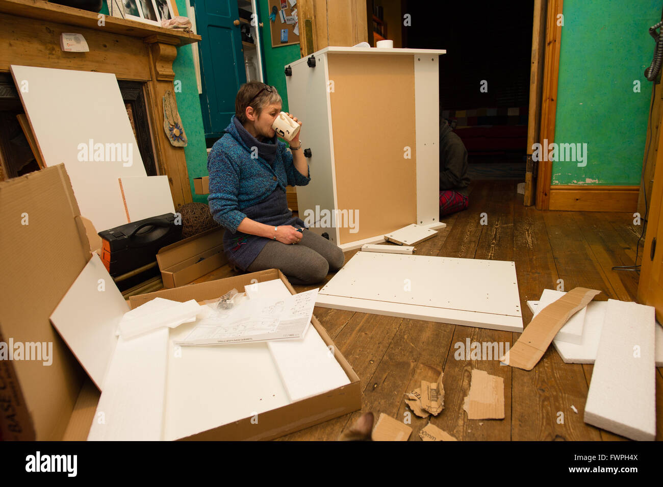 A middle-aged woman preparing to assemble a set of flat-pack ...