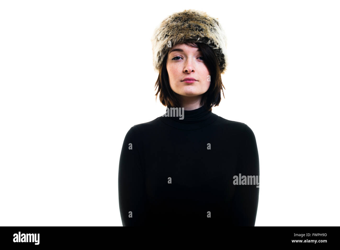 Haughtiness: A young person, woman girl, late teens early twenties, slim, brown hair, wearing a fur hat, looking - Stock Image