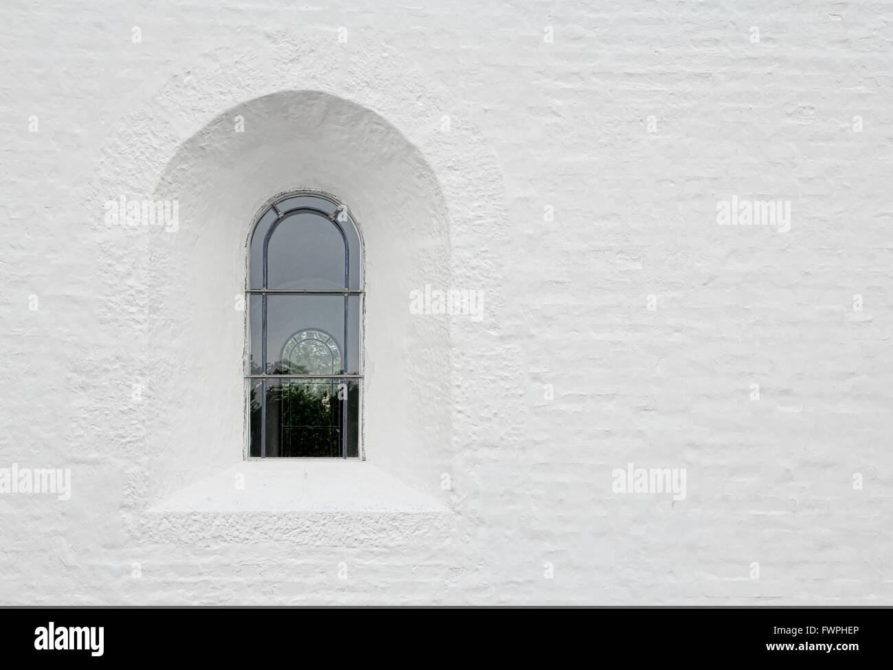 Arched leaded window in a white church wall - Stock Image