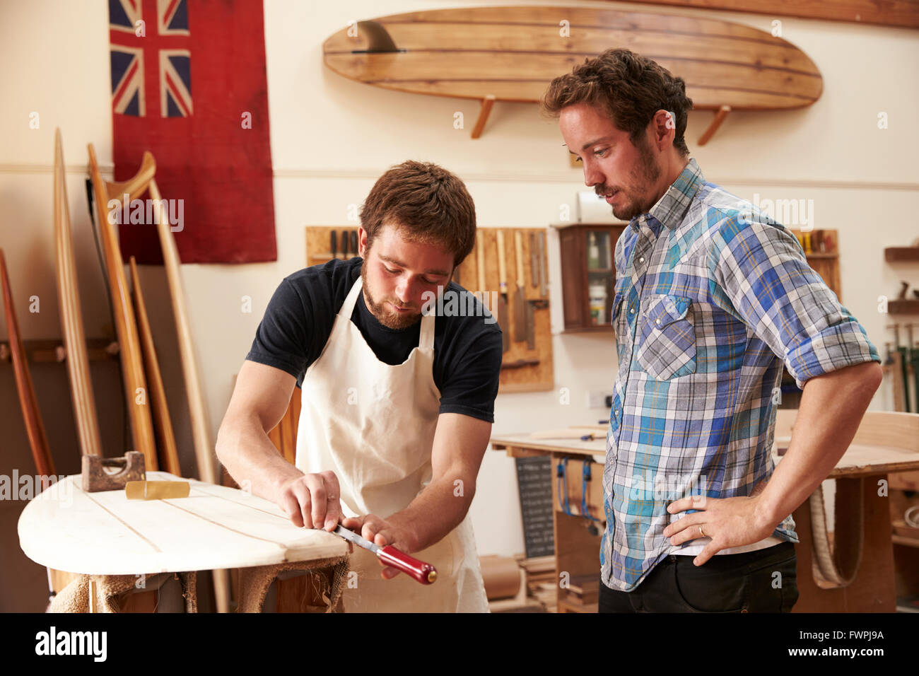 Carpenter With Apprentice Making Bespoke Wooden Surfboard - Stock Image