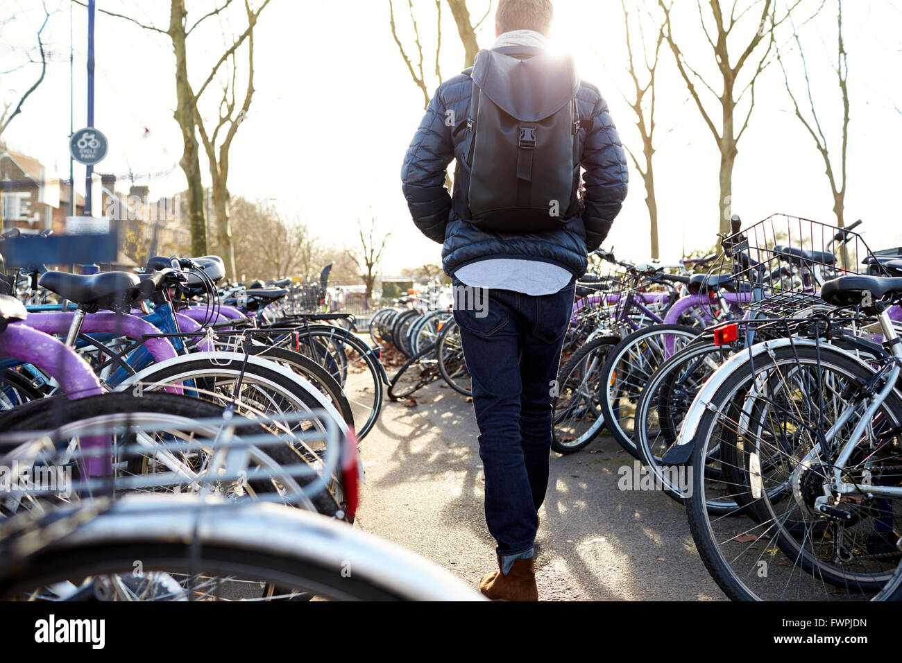 Rear View Of Man Leaving Bike In Cycle Park At Rail Station - Stock Image