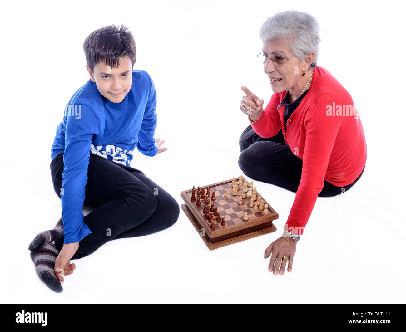 Grandmother with her grandson playing chess. White background. - Stock Image