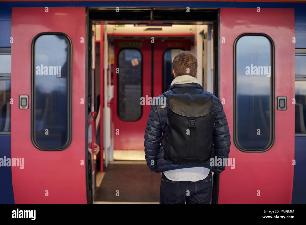 Man Standing On Railway Platform Waiting To Board Train - Stock Image