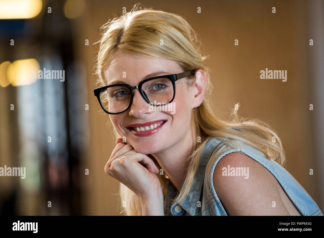 Beautiful woman in spectacle with hand on chin - Stock Image