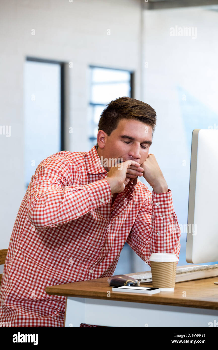 Man yawning at his desk - Stock Image