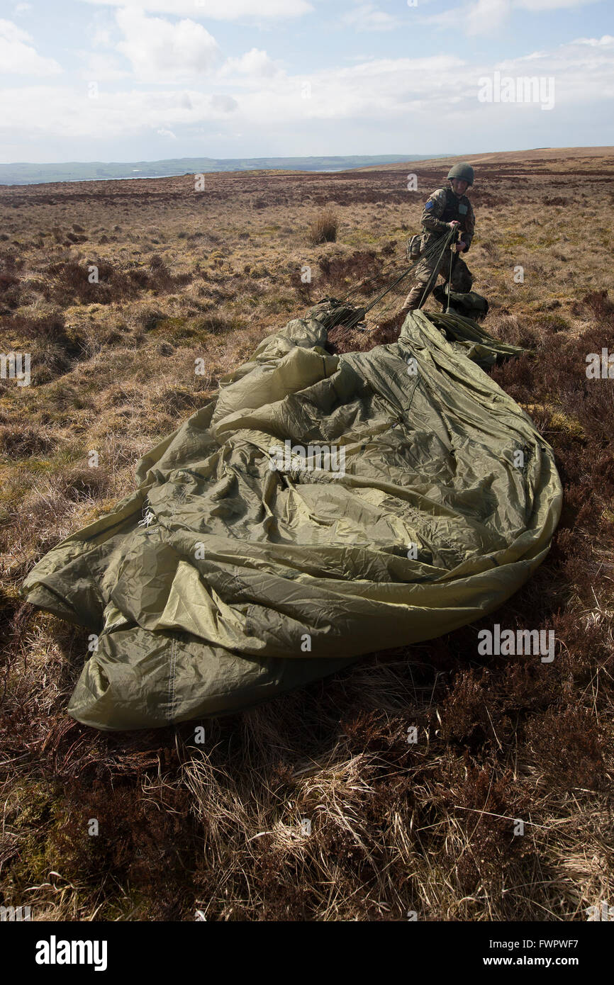 A British Army commando soldier pulls on his parachute while on an exercise on the Scottish moors. - Stock Image