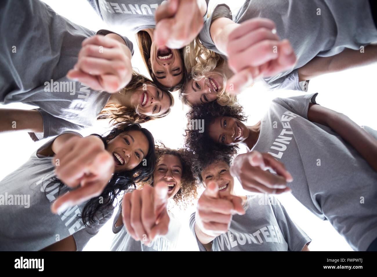 Happy volunteers pointing downwards - Stock Image