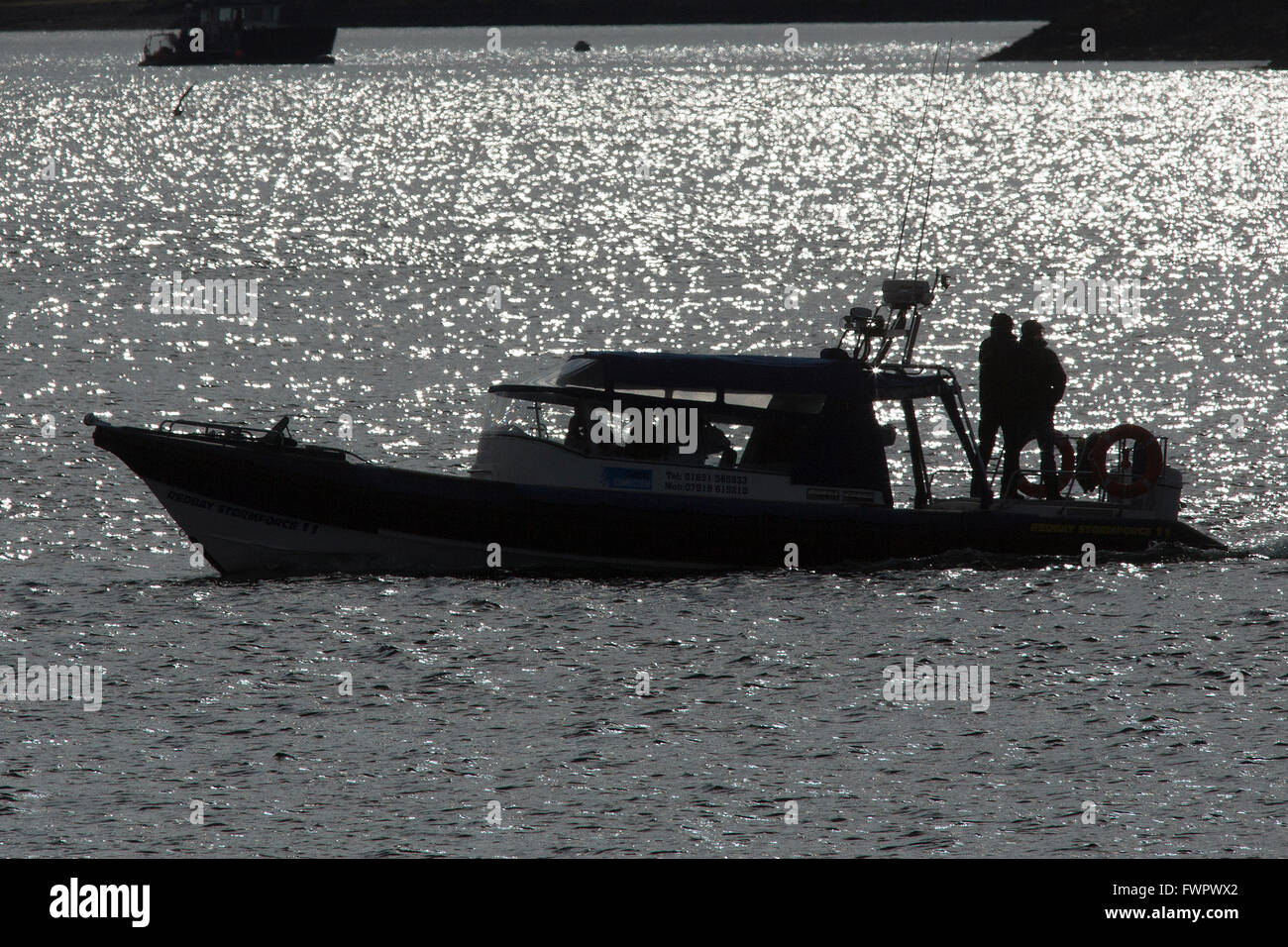 A small boat in silhouette. - Stock Image