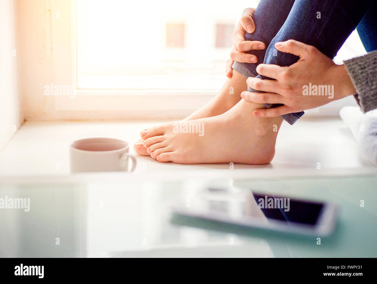 Feet of unrecognizable woman sitting on window sill - Stock Image