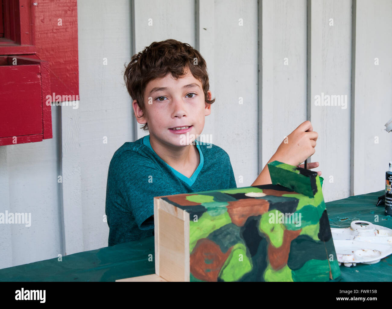 boy at camp painting a birdhouse craft project Stock Photo