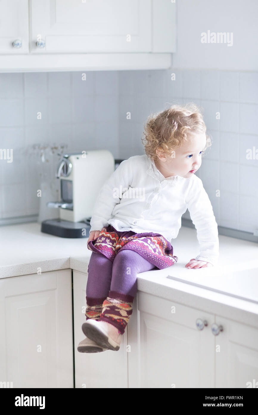 Adorable toddler girl sitting in a white kitchen on the counter top ...