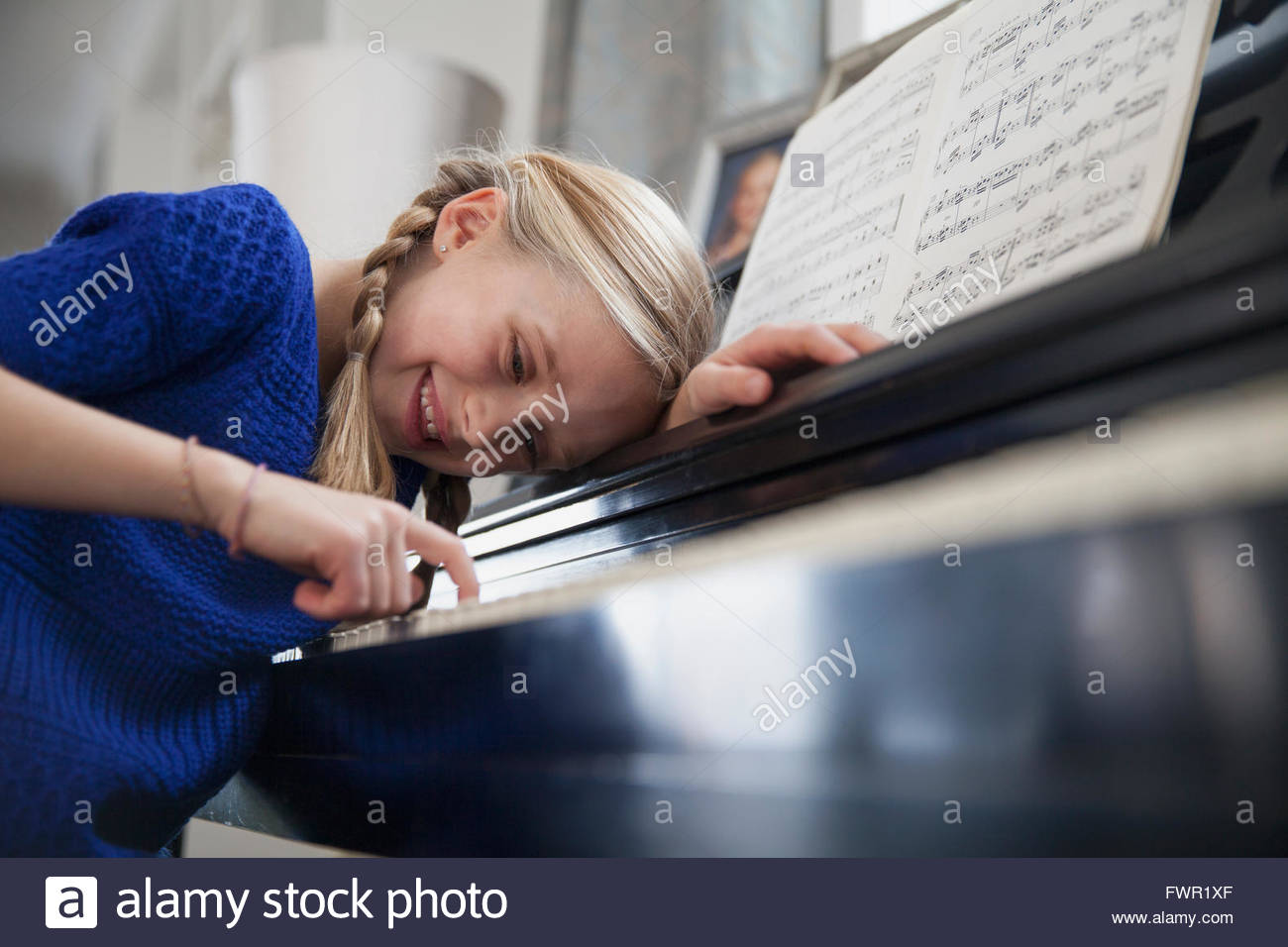 Happy young girl playing piano at home - Stock Image