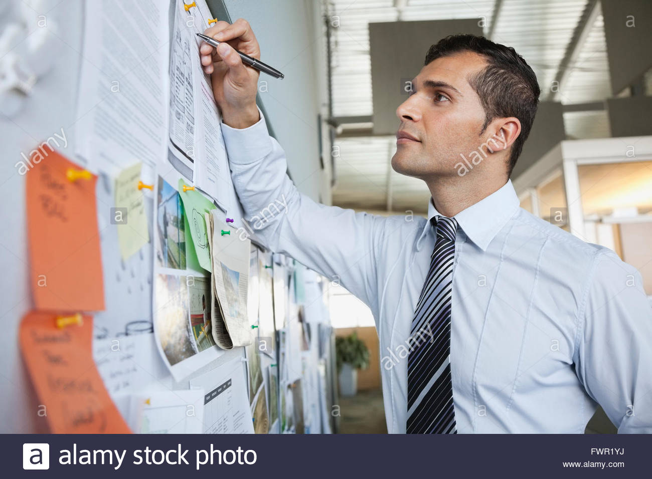 Businessman writing on notice board - Stock Image
