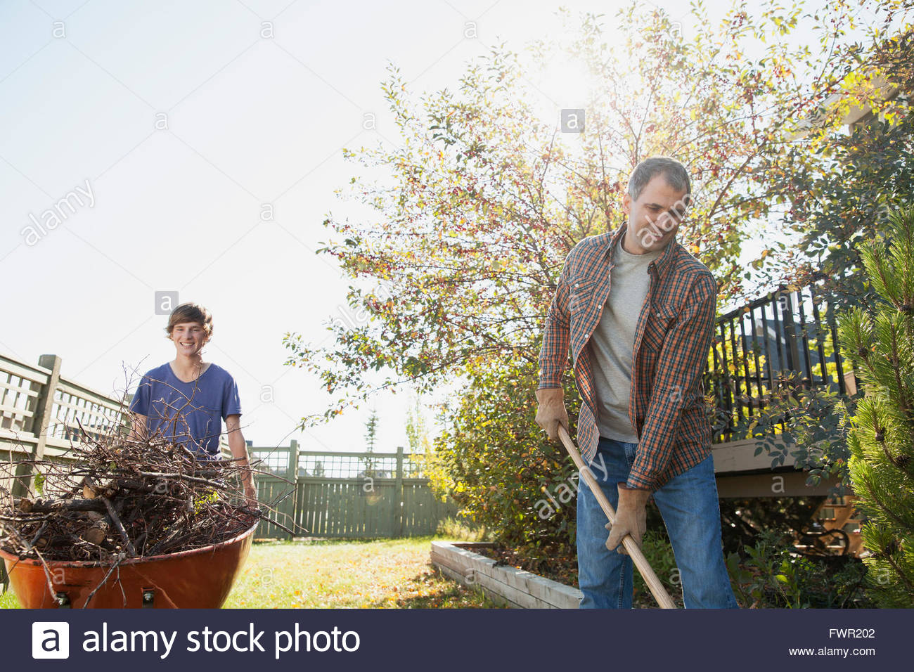 Father and son cleaning up yard - Stock Image