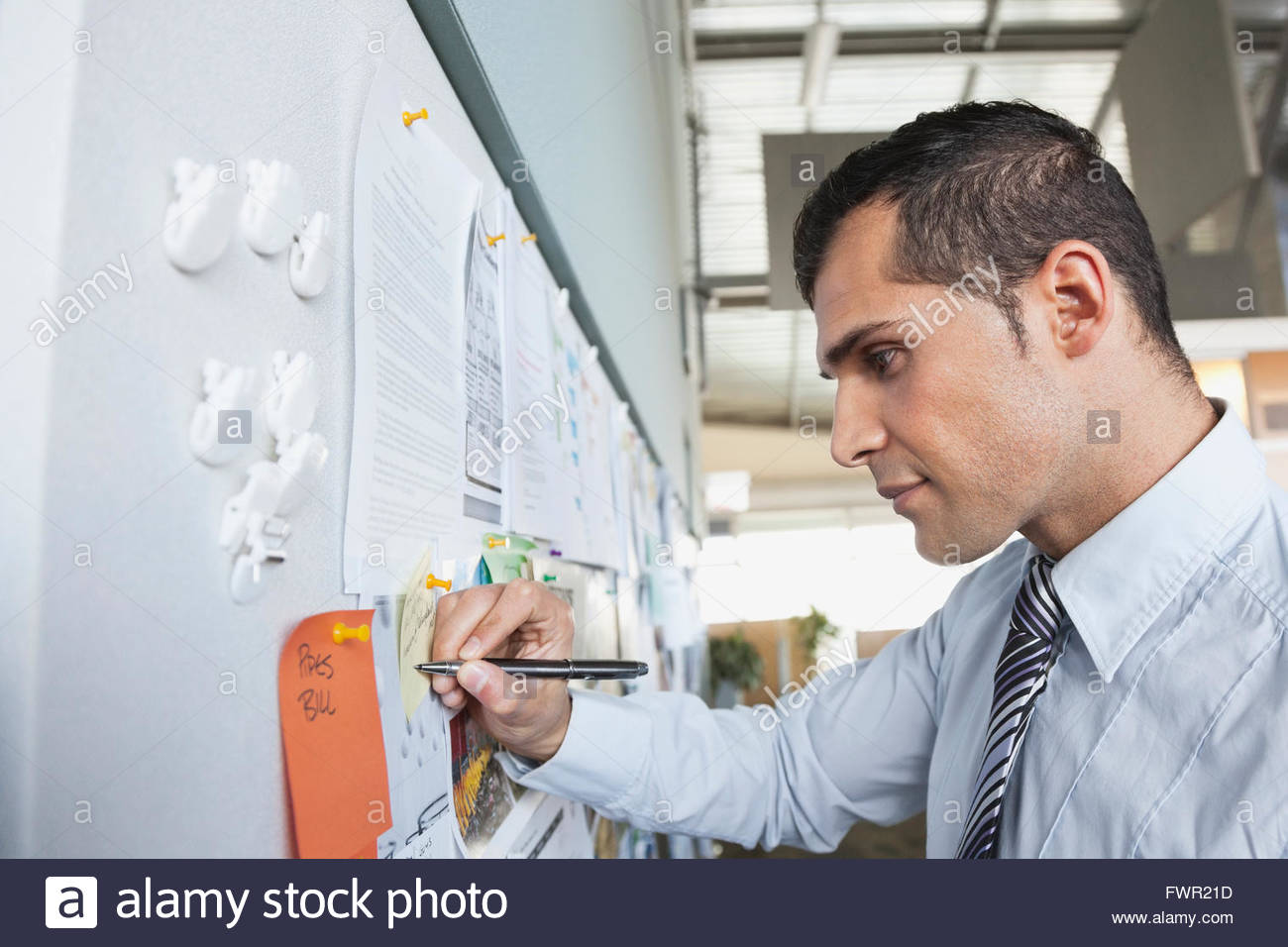 Businessman writing on notice board in office - Stock Image