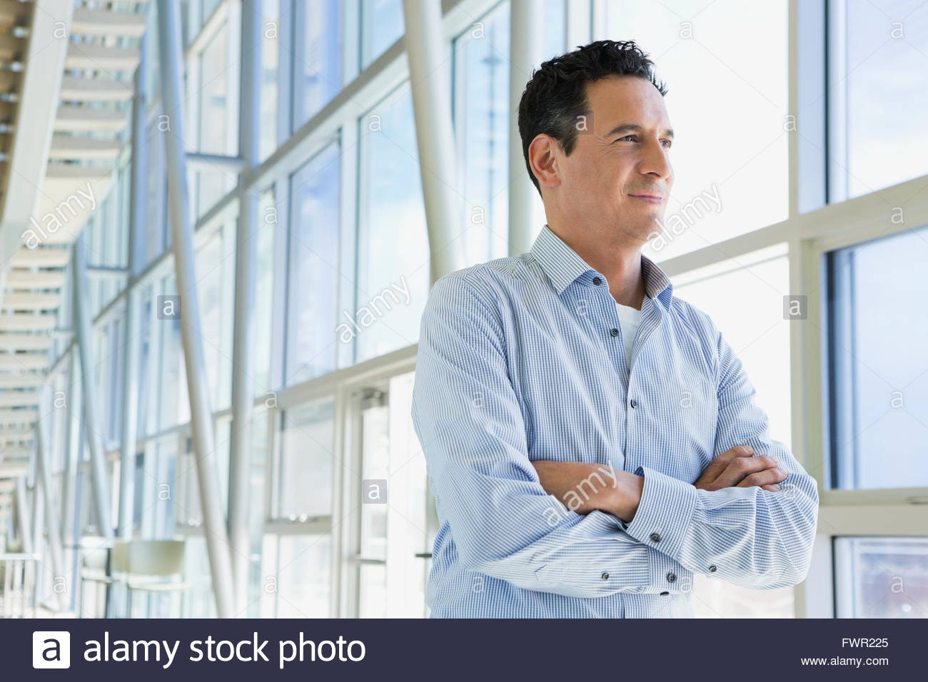 Businessman with arms crossed looking out window - Stock Image