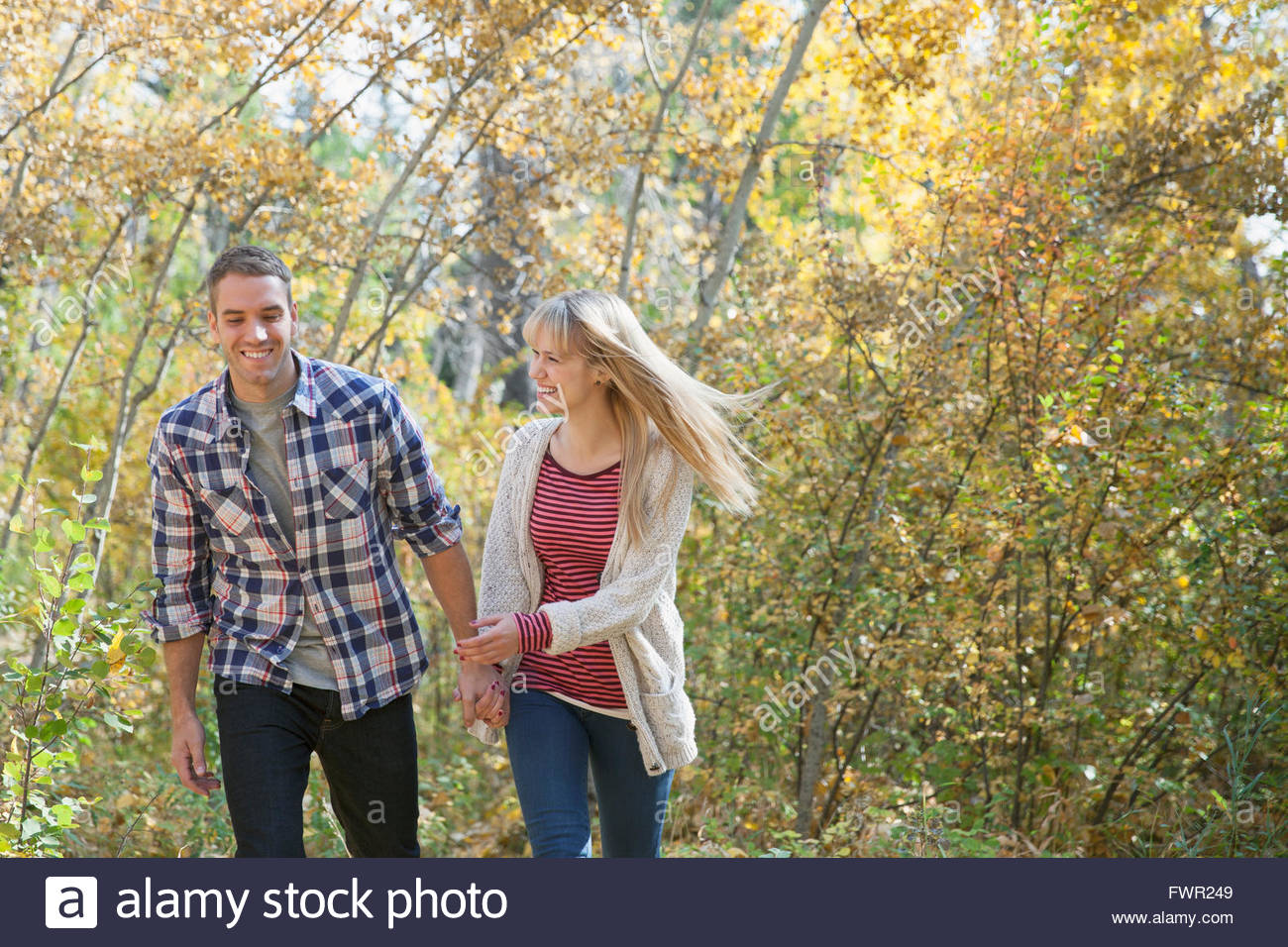 Happy young couple walking in park - Stock Image